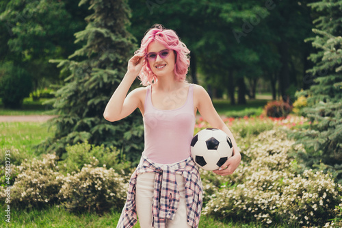 Fototapeta premium Photo of young sportive girl happy positive smile hold soccer ball player game park nature hand touch sunglass outdoors