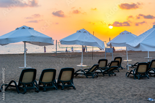 Fotografie, Tablou Umbrellas and sunbeds at sunset on sandy beach