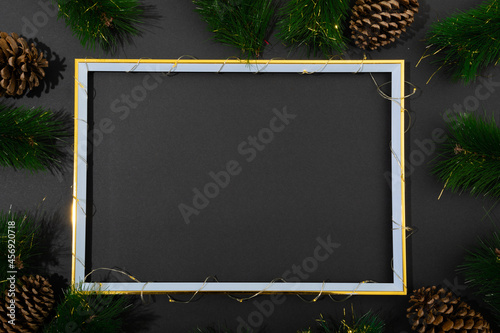 Fototapeta premium Composition of frame with copy space and fir tree branches with pine cones on black background