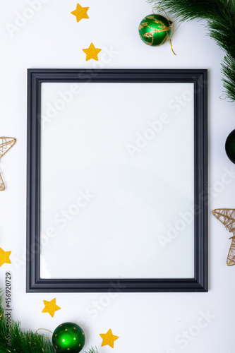 Fototapeta premium Composition of frame with copy space and fir tree branches with baubles on white background