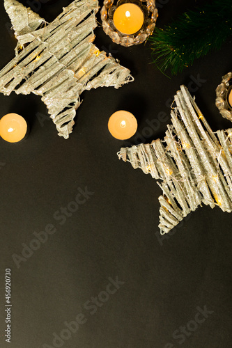 Composition of candles with tree branches, stars and copy space on black background