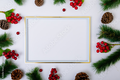 Fototapeta premium Composition of frame with copy space and fir tree branches with pine cones on white background
