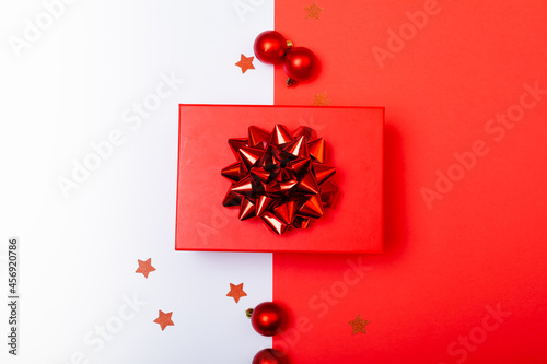 Composition of red present with baubles on white and red background