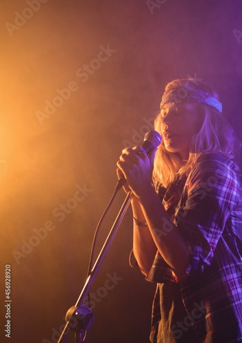 Caucasian female musician singing on a microphone at music concert