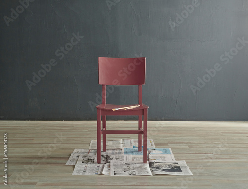 Fotografering Wood chair painting style, decorated on the newspaper design, Grey stone wall background