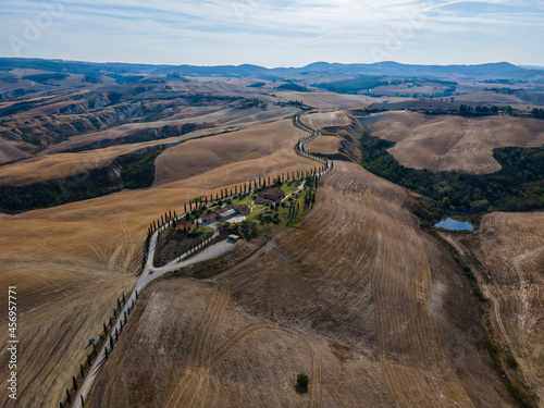 Fototapeta premium Aerial view of a scenic road with cypress trees on hilltop in Val d'Orcia in Tuscany, Italy.