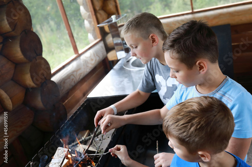 Fototapeta Three children kindle firewood in grill