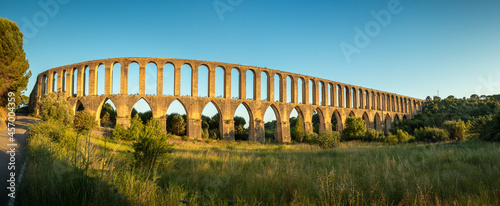 Foto Panoramic view of the Pegões aqueduct, near the city of Tomar in Portugal, with a field in the foreground, the blue sky in the background and the aqueduct illuminated by the sunset