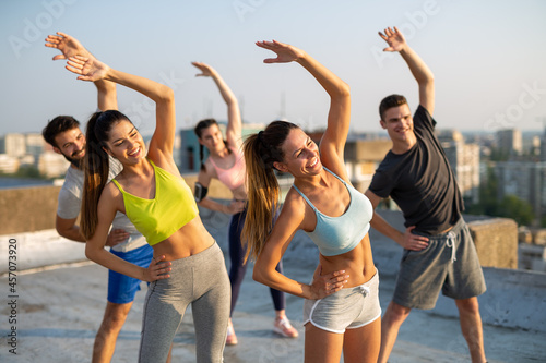 Fototapeta premium Group of happy friends working out together outdoors. Fitness, training, sport and people concept