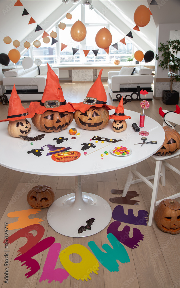 lot of pumpkins with painted faces on a table in a bright apartment