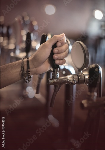 Close up view of hand holding beer tap at the bar