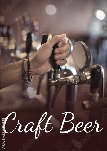 Craft beer text over hand holding beer tap at the bar