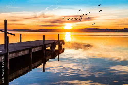 Obraz na płótnie viejo embarcadero en el lago debajo del atardecer