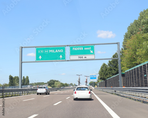 Fotografie, Obraz Highway sign with the names of the Italian cities of Milan and the exit road tow