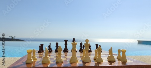Canvas A chessboard, in front of an infinity pool, overlooking the sea, during a sunny, summer day