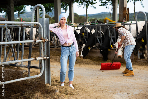 Fototapeta Portrait of successful young female breeder standing in cowshed..