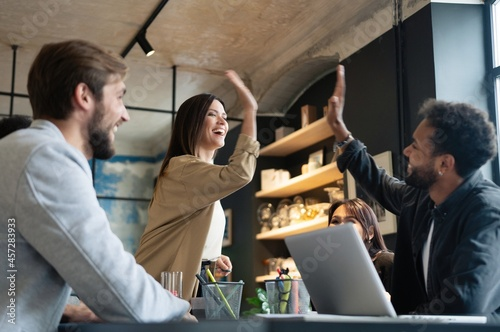 Two cheerful young business people giving high-five while their colleagues looking at them and smiling Fototapet