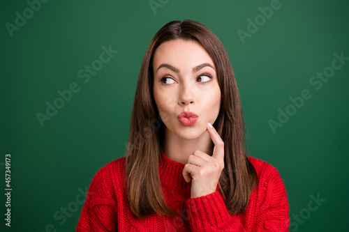 Photo portrait smiling girl wearing knitted sweater curious pouted lips got idea isolated green color background
