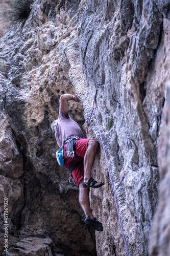 Obraz na płótnie Ucranian man climbing a tufa rock in spain