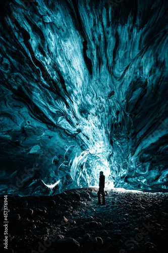 Fototapeta Person is standing in beautiful ice cave  in Vatnajökull glacier Iceland in the