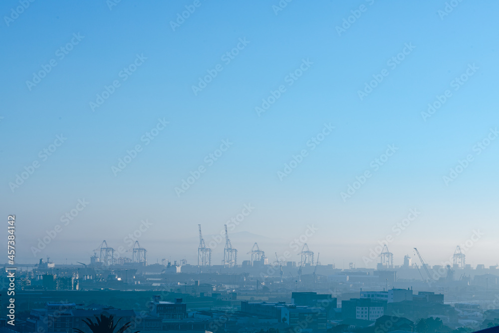 General view of cityscape with multiple modern buildings and cranes in the morning