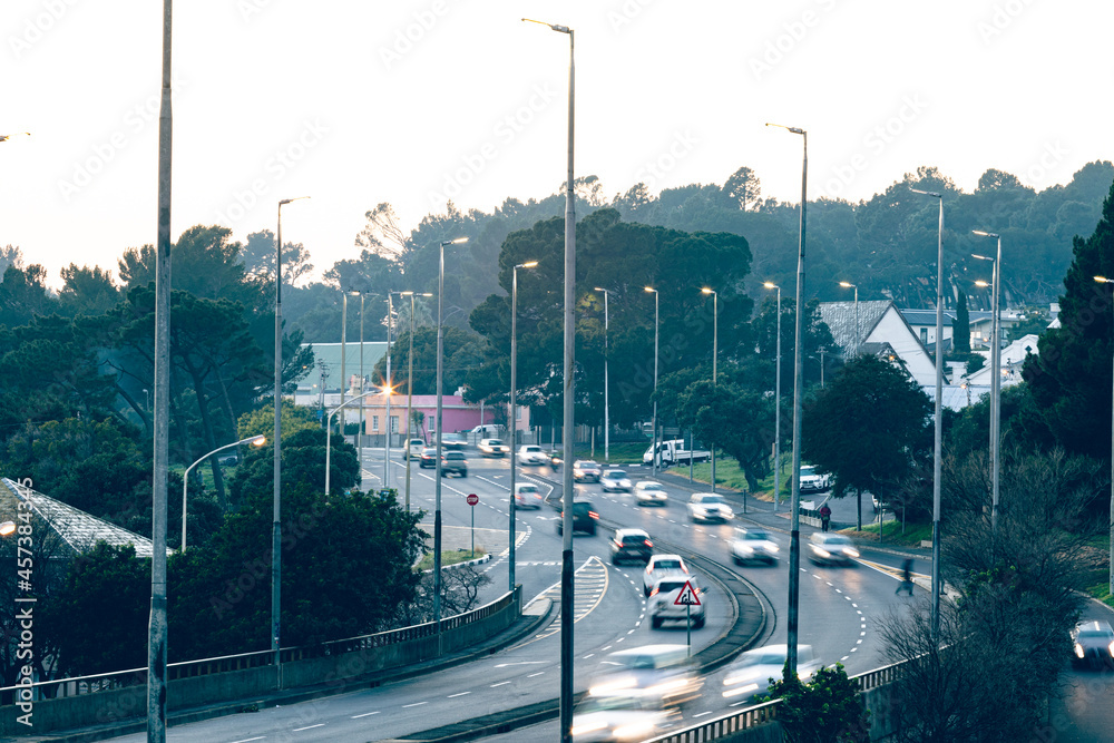 General view of cars driving through street in suburbs in the morning