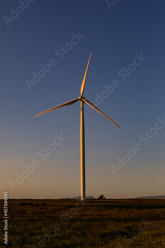 General view of wind turbine in countryside landscape during sunset