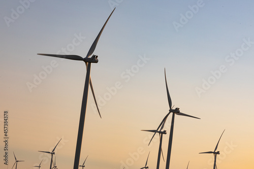 General view of wind turbines in countryside landscape with cloudless sky