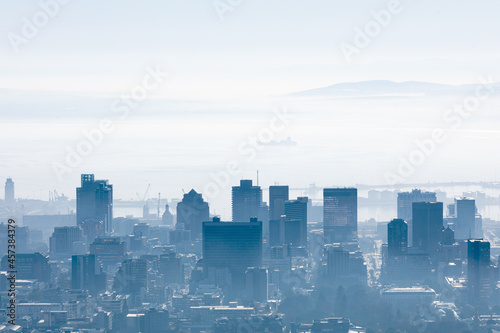 General view of cityscape with multiple modern buildings and skyscrapers in the foggy morning