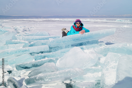 A woman of 35-40 years old lies on an ice hummock on the ice
