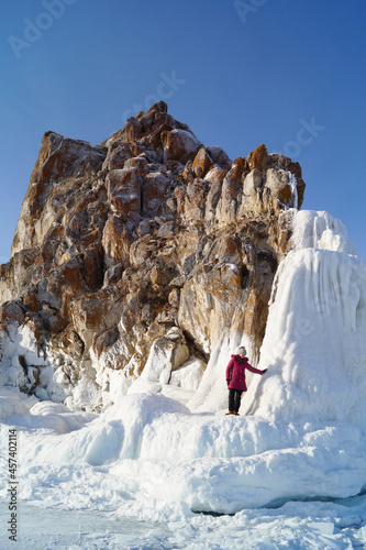 View of the icy rock Shamanka and the girl standing on the ice