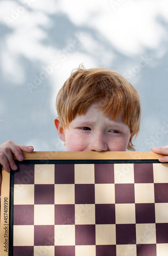 child with red hair plays chess