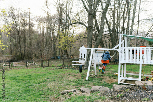 Two children swinging together at sunset in backyard in spring