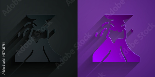 Paper cut Volcano eruption with lava icon isolated on black on purple background Fototapeta