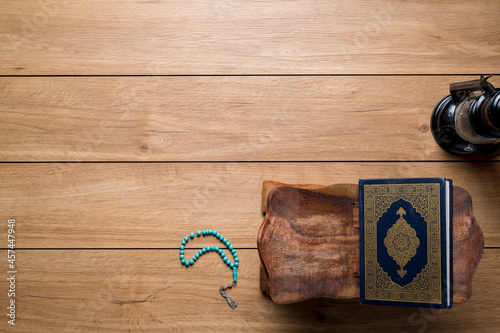 Fototapeta Islamic concept - The Holy Al Quran with written Arabic calligraphy meaning of Al Quran and rosary beads or tasbih and an Arabian lamp, on wooden stand, with copy space