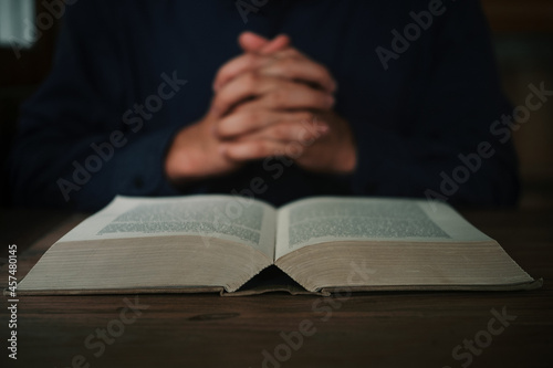 Fotografie, Obraz Man is reading and praying the scripture or holy bible on a wooden table with copy space