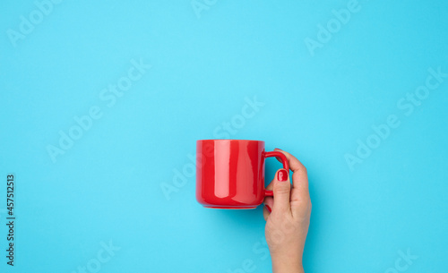 Fotografering red ceramic cup in a female hand on a blue background, drink and hand are raised