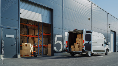 Obraz na plátně Outside of Logistics Warehouse with Open Door, Delivery Van Loaded with Cardboard Boxes