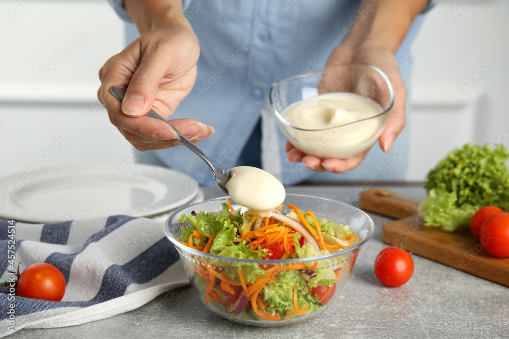 Leinwandbild Motiv - New Africa : Woman adding mayonnaise to delicious salad at grey table, closeup