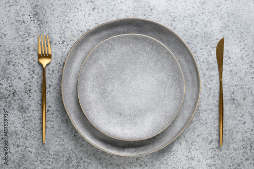 Obraz na plátně Elegance empty table setting with empty gray plate with golden cutlery as mockup on grey stone background