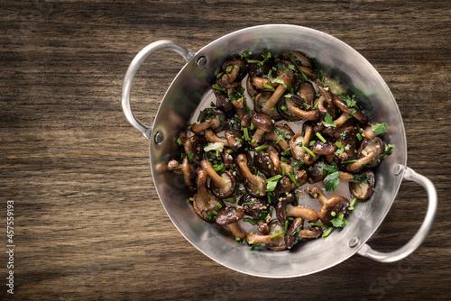 Fotografie, Obraz Shiitake mushrooms sauteed with garlic and herbs in metal pan