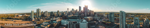 Fotografiet A panoramic image of downtown building and tower skyline against a shining sun and beautiful blue skies