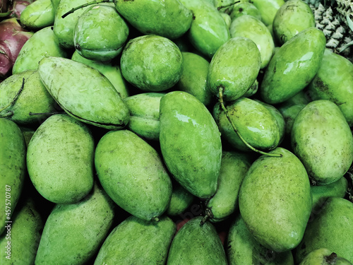 Fototapeta Pile of Fresh Green Mango Fruits for Sale at Market Stall