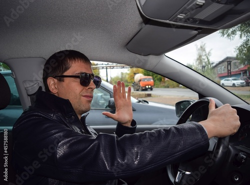 A young man with glasses is sitting at the wheel of a car, smiling and waving hi Fototapet