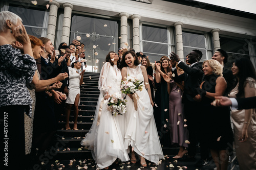 Fotografiet Candid shot of two female lesbian LGBT brides walking down the stairs during the