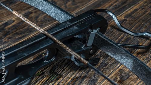 Obraz na plátně Part of modern compound crossbow handgun on the dark wooden background