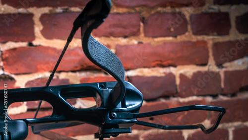 Fotografie, Obraz Part of modern compound crossbow handgun on the red brick wall background