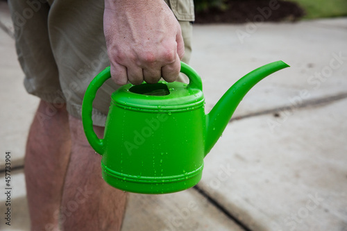 Fototapeta Man holding small green watering can
