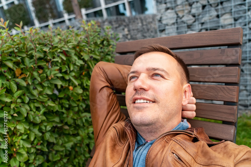 Slika na platnu Handsome man relaxing on wooden chaise lounge in city park