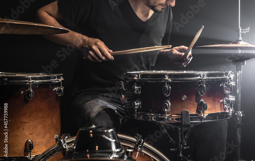 Fotografering A male drummer plays drums on stage.